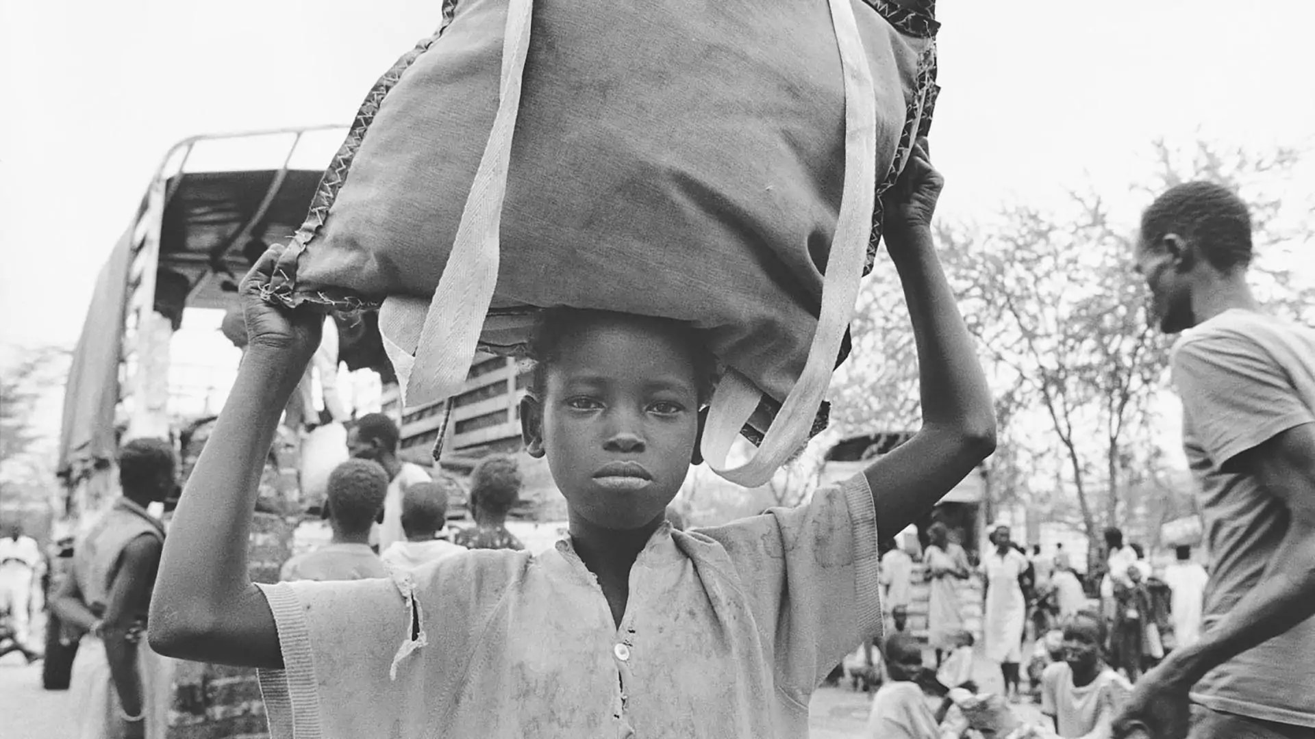 A young boy holds a package over his head while others surround a vehicle.