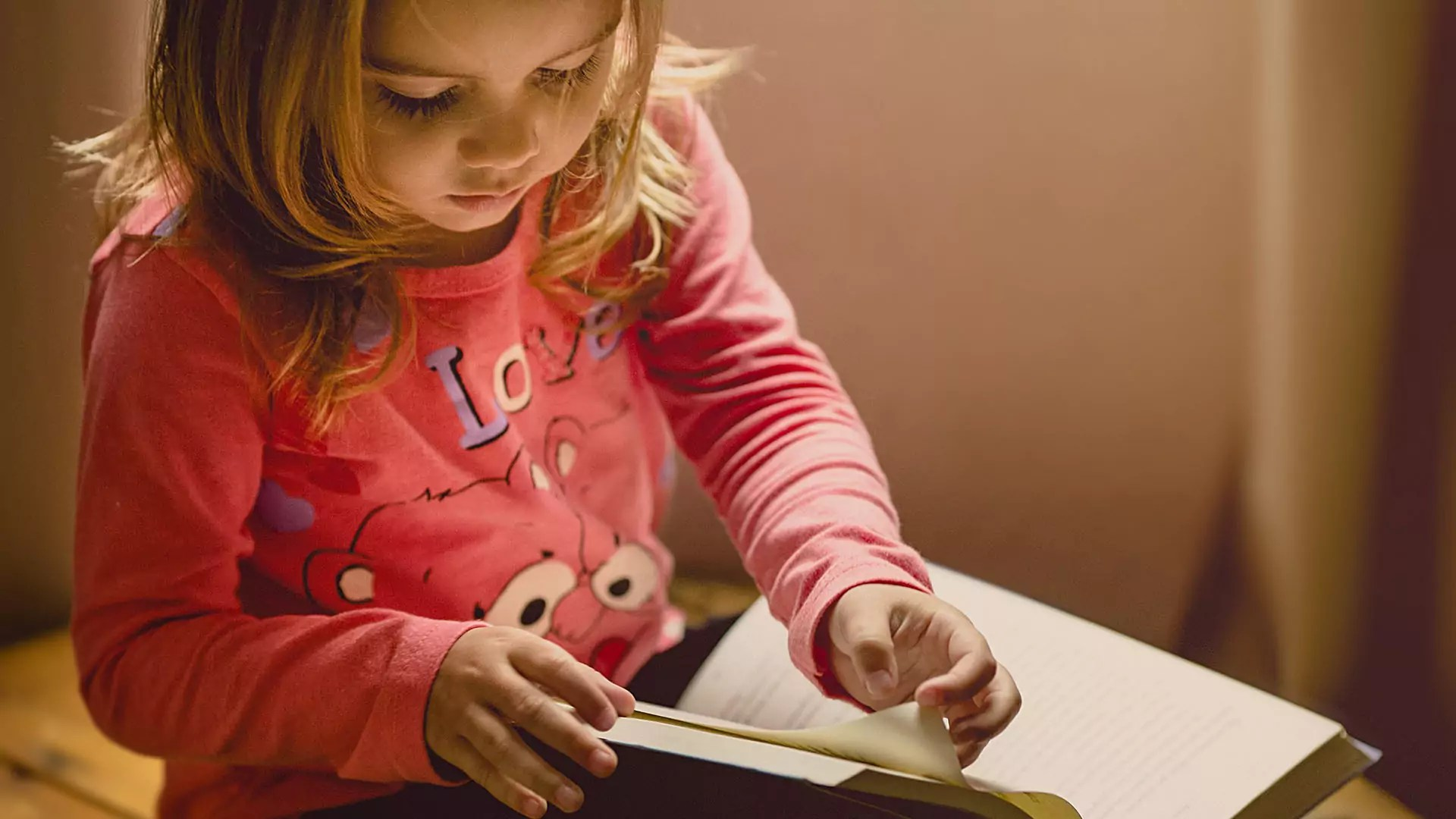 A small child flips through pages of a book.