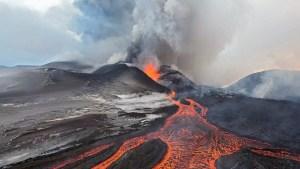 A volcano eruption, with molten lava trickling down it.