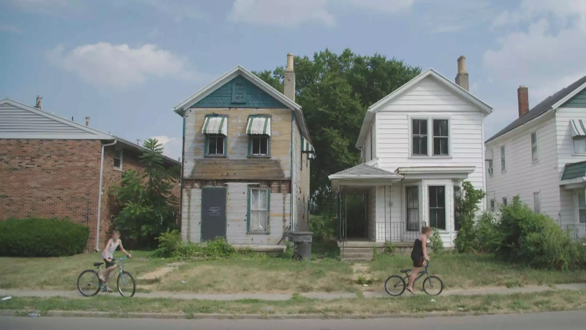 Two people on bicycles ride down a street in front of abandoned houses.