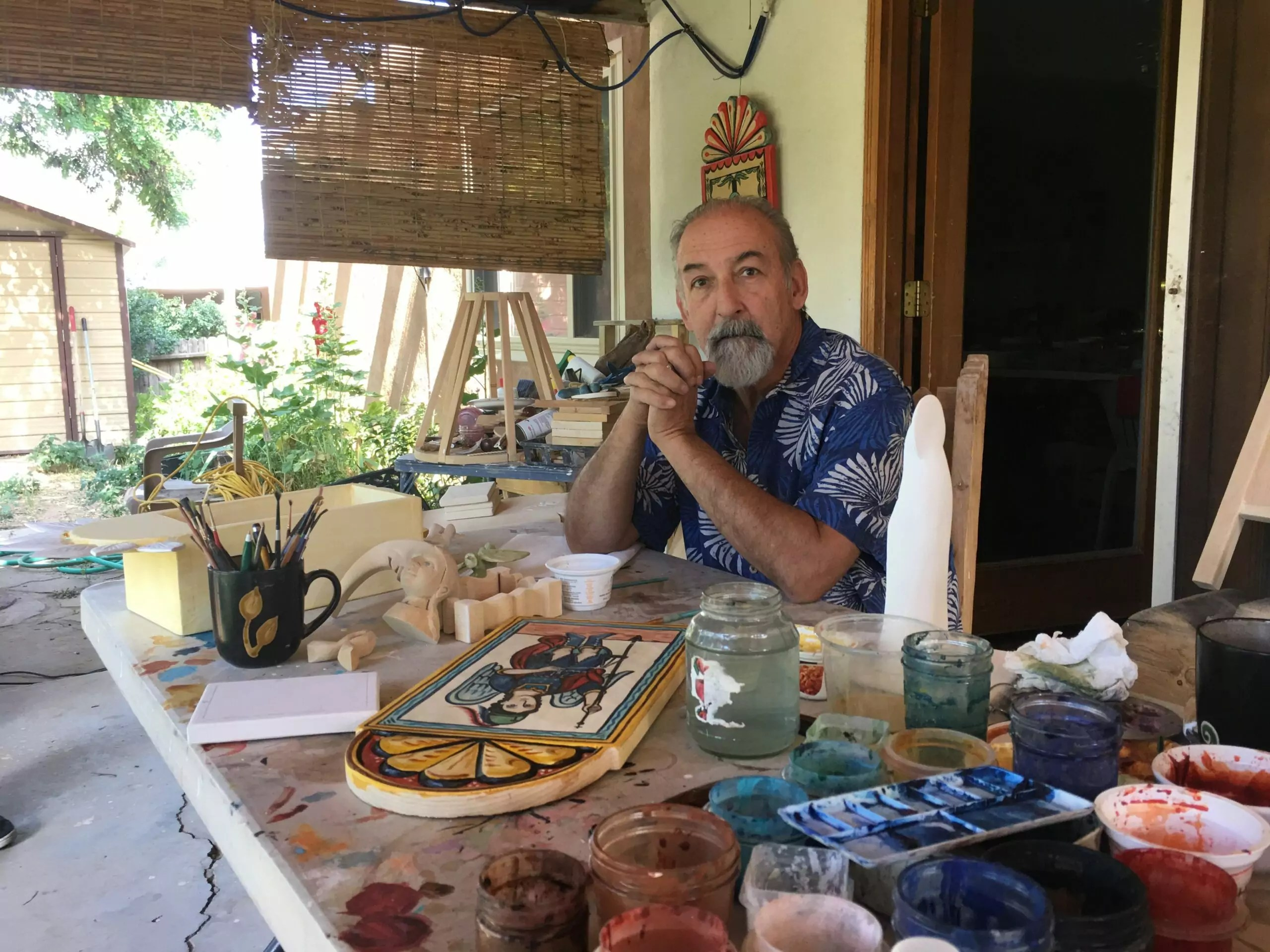 A man sits down at a table covered in art supplies.