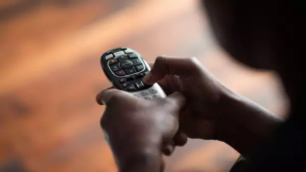 Two hands handle a remote control, with one finger pressing the fast forward button.