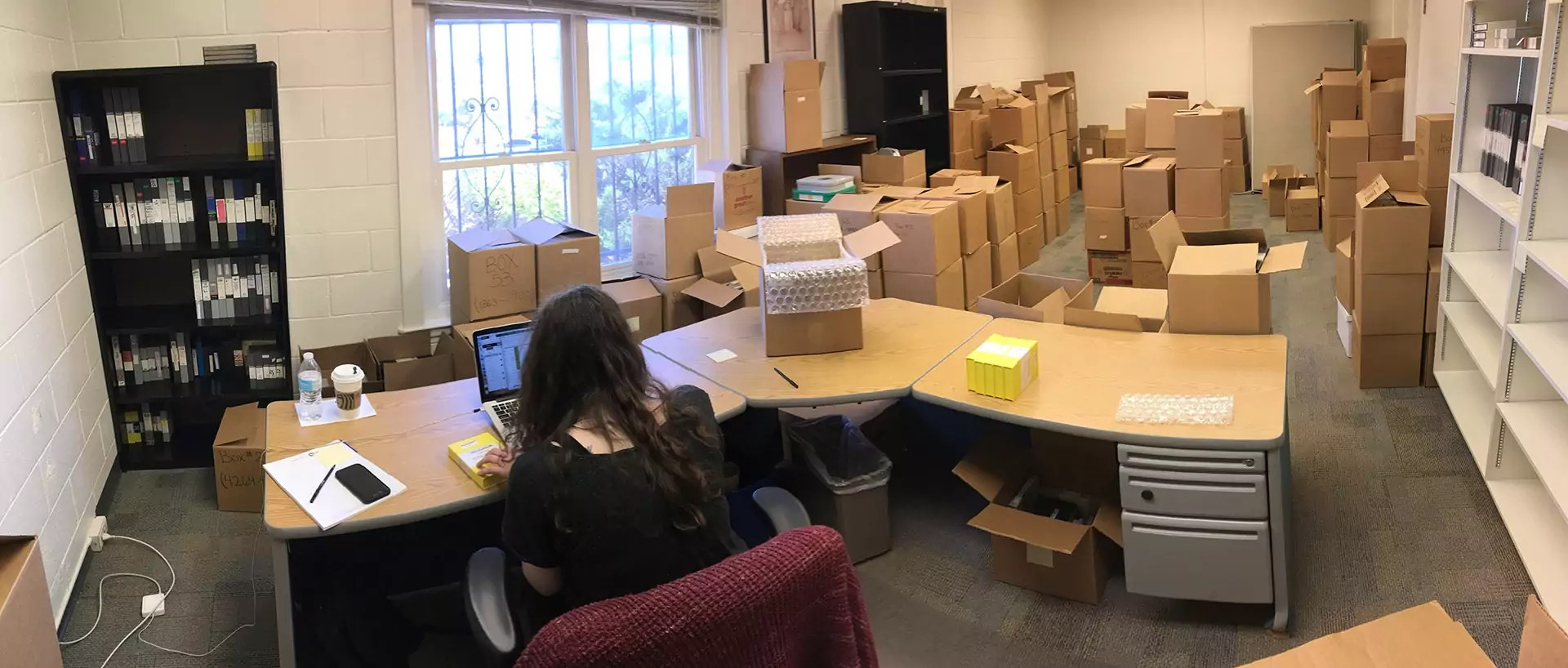 Archivist Megan Rose works at a desk to process boxes of media.