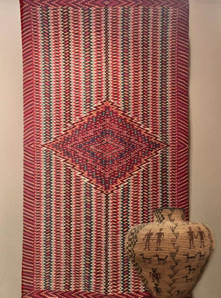 A detailed rug with sharp geometry woven into it.