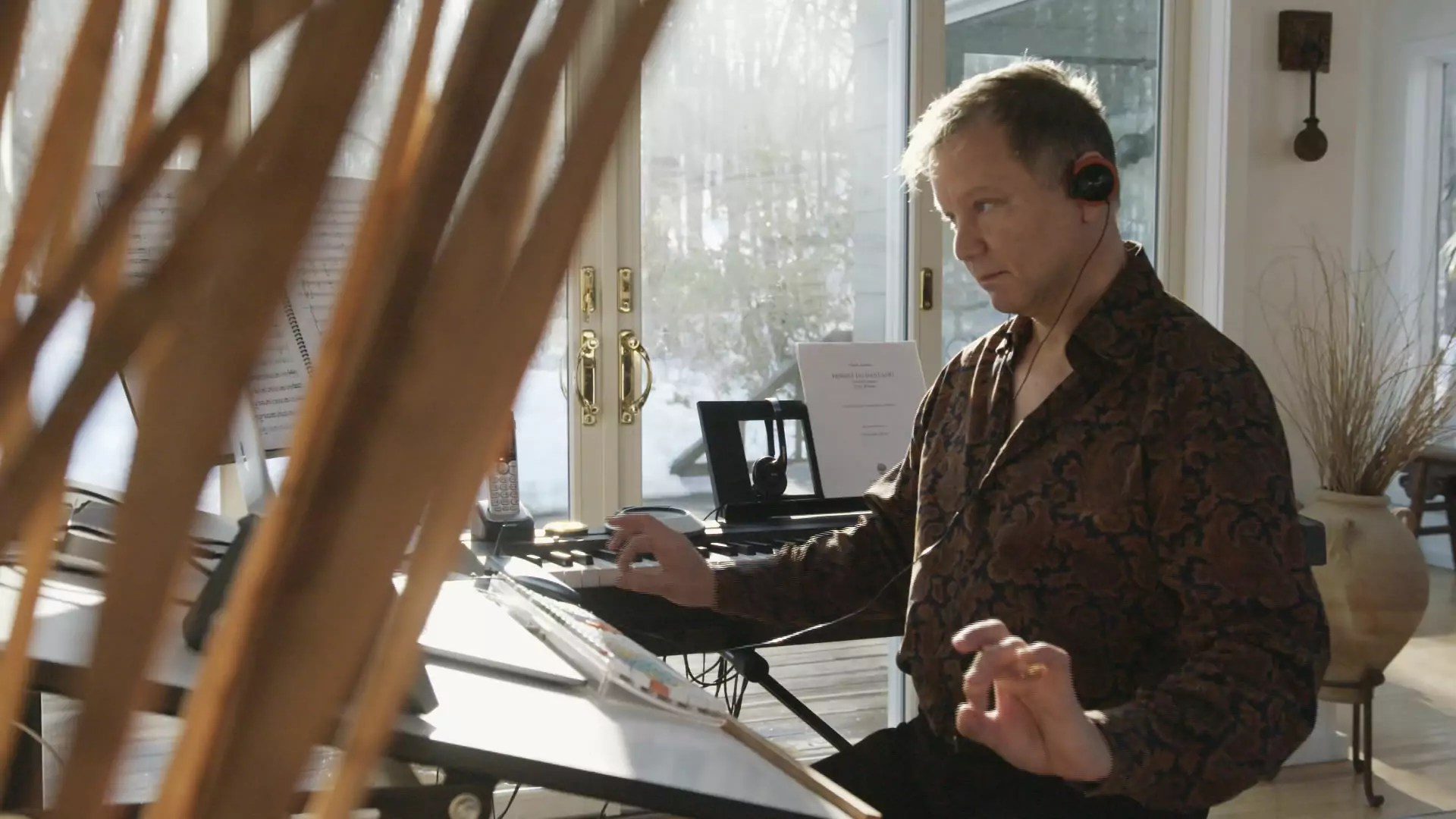 A man sits at a desk composing and listening to music.