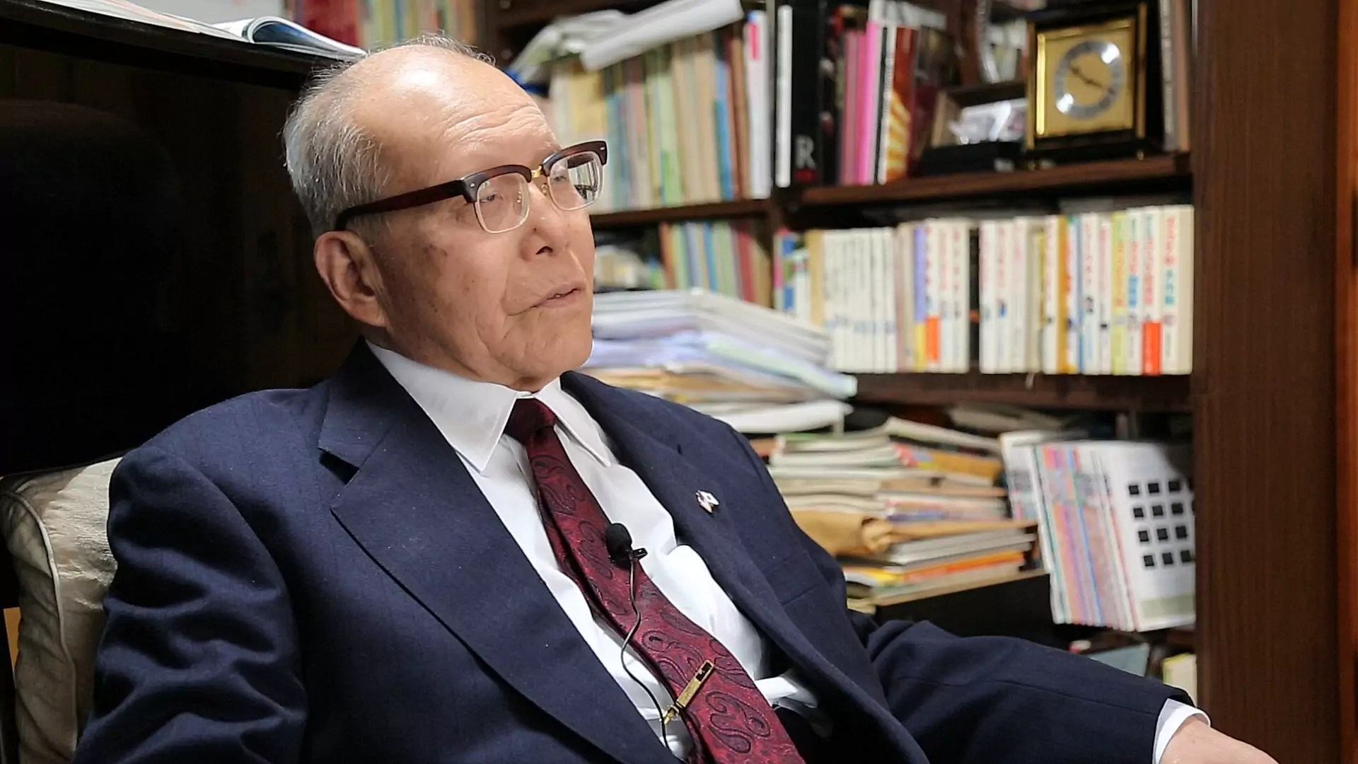 A man wearing a suit and glasses sits in a library