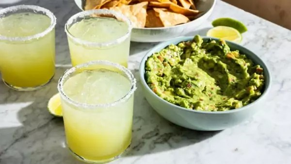 Three glasses of margaritas and bowls of guacamole and chips