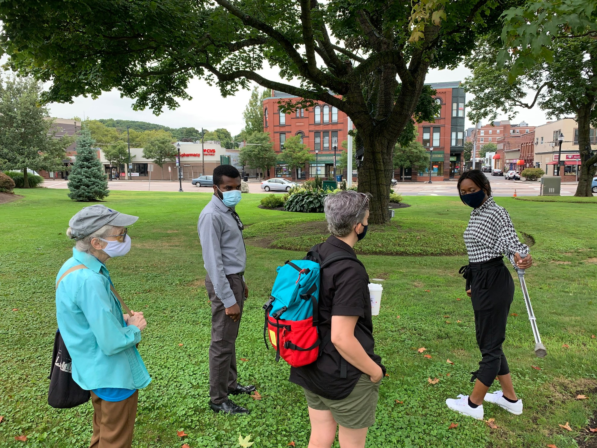 four people consult outdoors about the moving play route