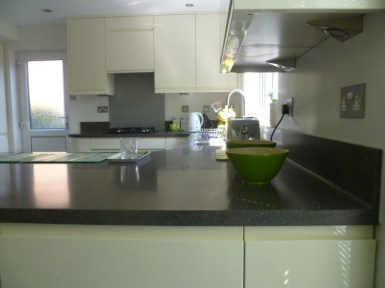 Lava Rock corian worktop in handleless gloss kitchen
