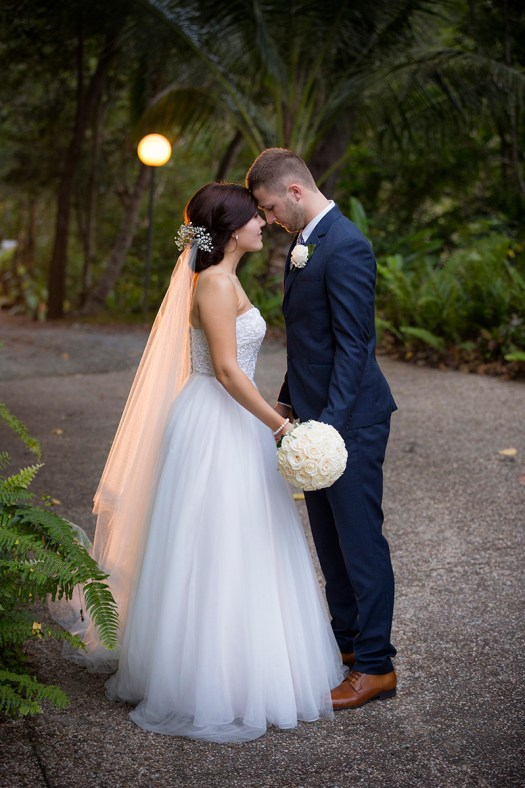 Full length of bride and groom on sealed track in a domestic rainforest setting. Wedding photography Cairns Australia by excitations.