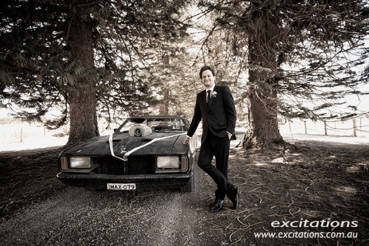 Brown toned image of a groom posing with a car from the original Mad Max movie. Full length wedding photography by Excitations of Mildura.