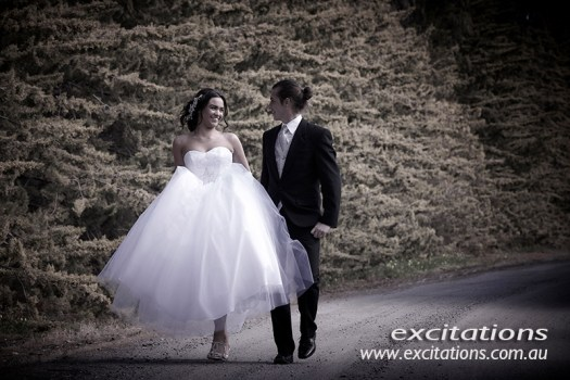 Another in the series debutantes ohn location. Full length walking sho of debutante and her partner walking beside a mature row of conifers. Photography in Mildura by Excitations.