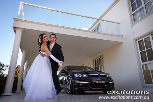 Debutantes on location by excitations mpotographer Mildura. Deb and her partner haming it up in front of stunning white house and a awesome black sports car.