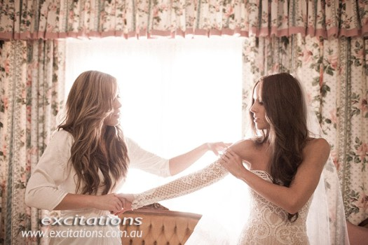 Mildura wedding photos. Bride and bridesmaid preparing for a wedding. grainy soft image by Excitations Mildura photographers.