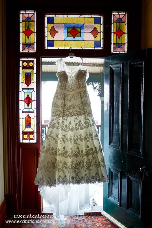 Bides dress hanging in doorway. Broken Hill wedding by Excitations.