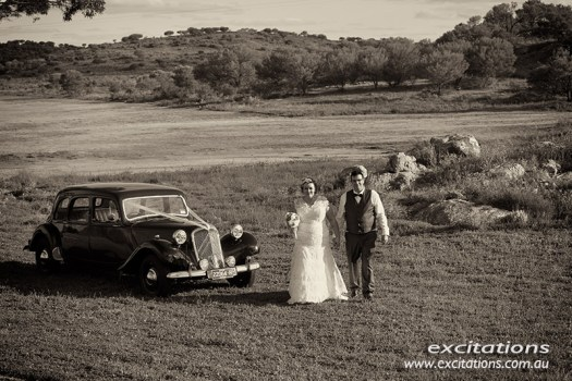 Toned wedding portrait of bride and groom with vintage car. Broken Hill wedding photos by Excitations.