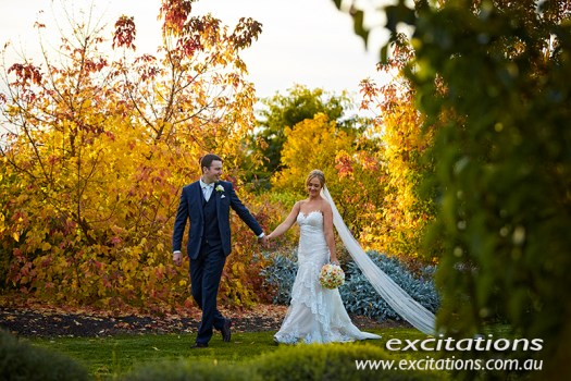 Mildura wedding photos by Excitations. Bride and groom walking through Autumn coloured garden.
