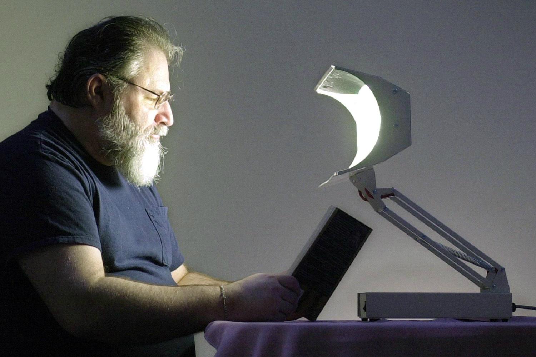 man reads by light that treats seasonal affective disorder