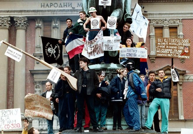 Serb youths show anti NATO banners during a concert against NATO airstrikes  on Belgrade's central square during an air raid alert, Monday, March 29, 1999. Thousands of people attended  the concert in Republic Square as NATO continues airstrikes for the sixth consecutive day. (AP PHOTO /str) YUGOSLAVIA OUT