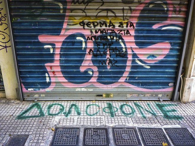 Συνθήματα έξω από το κοσμηματοπωλείο στην οδό Γλάδστωνος στην Ομόνοια όπου βρήκε το θάνατο ο 33χρονος Ζακ Κωστόπουλος
