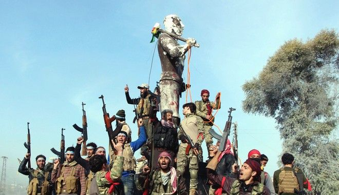 "Turkey-backed Free Syrian Army soldiers celebrate around a statue of Kawa, a mythology figure in Kurdish culture as they prepare to destroy it in city center of Afrin, northwestern Syria, early Sunday, March 18, 2018. Turkey's President Recep Tayyip Erdogan said Sunday that allied Syrian forces have taken ""total"" control of the town center of Afrin, the target of a nearly two-month-old Turkish offensive against a Syrian Kurdish militia, which said fighting was still underway. Erdogan said the Turkish flag and the flag of the Syrian opposition fighters have been raised in the town, previously controlled by the Kurdish militia known as the People's Defense Units, or YPG. (Hasan Krmzita/DHA-Depo Photos via AP)"