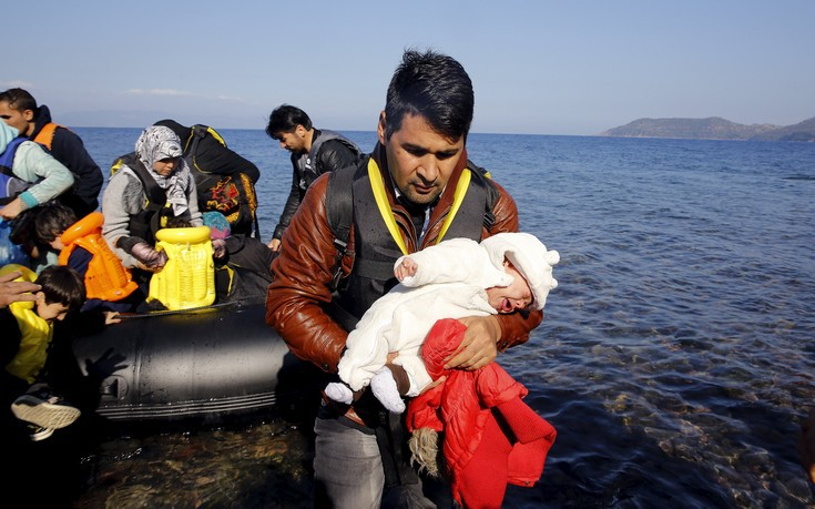 An Afghan migrant carries his one-month-old child as he disembarks from an overcrowded raft at a beach on the Greek island of Lesbos October 19, 2015. Thousands of refugees - mostly fleeing war-torn Syria, Afghanistan and Iraq - attempt daily to cross the Aegean Sea from nearby Turkey, a short trip but a perilous one in the inflatable boats the migrants use, often in rough seas. Almost 400,000 people have arrived in Greece this year, according to the U.N. refugee agency UNHCR, overwhelming the cash-strapped nation's ability to cope. REUTERS/Yannis Behrakis