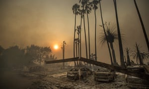 Smoke rises behind a destroyed apartment complex and burned out cars after the Thomas fire ripped through Ventura, California