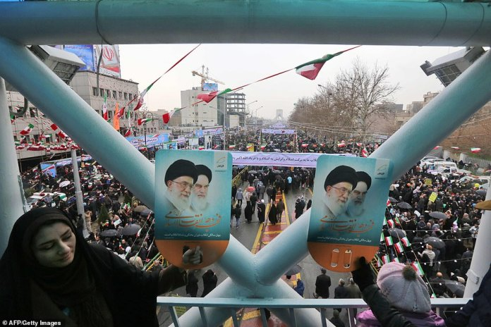 A woman holds up a sign showing portraits of the country's Supreme Leader Ali Khamenei and his predecessor  above the rally