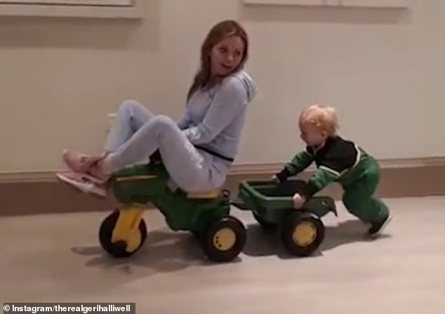 Strength to strength: Geri Horner showed her son was growing up fast as she shared a playful clip of him pushing her along in a mini tractor on Tuesday