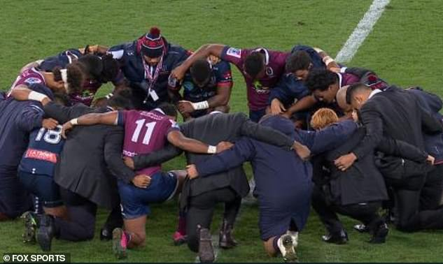 Christian Reds and Rebels players huddle on the pitch after their match last weekend in solidarity with Folau