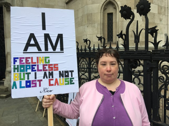 Ciara Lawrence stands outside the Royal Courts of Justice holding a placard that says 'I am feeling but hopeless but I am not a lost cause""