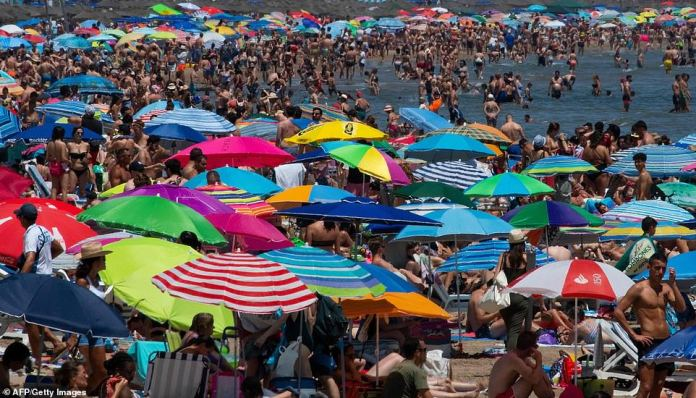 People swarm a public beach amid a heatwave in Valencia amid blazing temperatures across Spain. The southern European nation has been among the worst hit by the heatwave