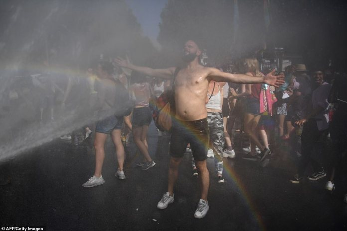 Police used hoses to keep people cool as they marched through the streets of Paris for the Pride festival despite the soaring temperatures