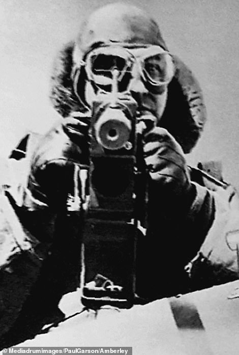 A German soldier operating a camera much as he might use a gun, staring down the viewfinder with the lens pointed straight ahead. A German caption reads: 'Aiming with the camera works exactly the same as shooting'.