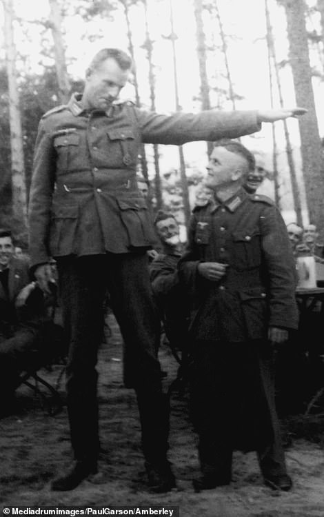 Two German soldiers compare heights - with one of them almost two heads taller than the other