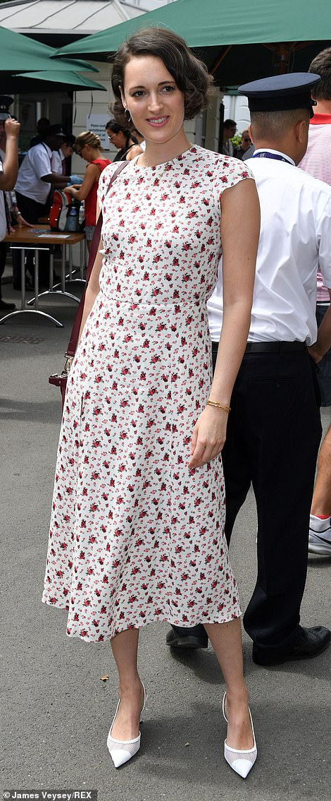 Leggy: The high-necked dress cinched in at her slender waist before flowing into a chic mid-length skirt