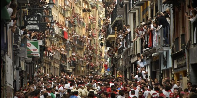 Revellers run next to fighting bulls from Cebada Gago ranch during the running of the bulls at the San Fermin Festival, in Pamplona, northern Spain, Monday, July 8, 2019. (AP Photo/Alvaro Barrientos)