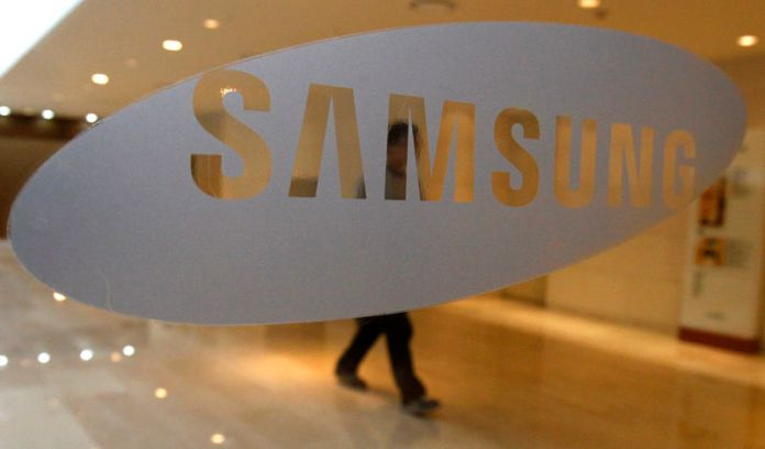 © Reuters. FILE PHOTO: A man walks behind a logo of Samsung Electronics at the company's headquarters in Seoul