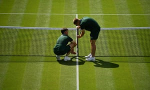 Ground staff set up the net on an outer court.