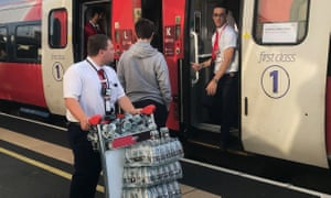An LNER staff member provides bottled water for passengers stranded at Peterborough station.