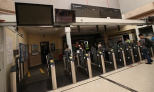 People walk through Clapham Junction station where the information boards and ticket machines were not working.