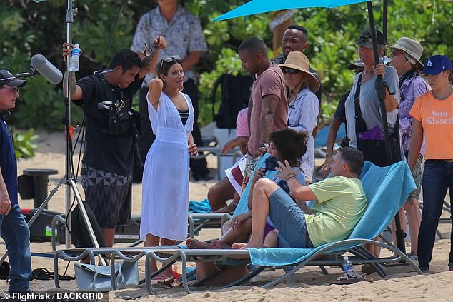 Chitchat: Lea was wearing her swimsuit with a thin white robe whilst filming her beach scene with Nia and Charles, who lounged on deck chairs