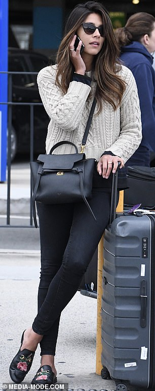 Casual chic: She was seen chatting on her phone, while dressed casually in a woolen jumper, tight black jeans and flat shoes