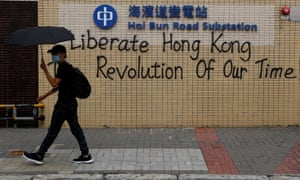 A demonstrator walks past graffiti as he marches during a protest in Hong Kong.