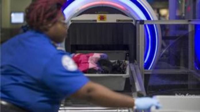 File image of an airport security worker helping travellers place their bags through the 3D scanner at the Miami International Airport in May 2019