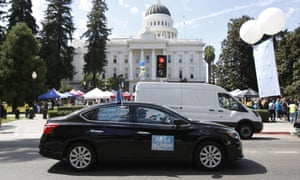 A rideshare driver supporting the AB5 bill drives past the California statehouse in Sacramento.