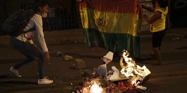 Supporters of opposition presidential candidate Carlos Mesa burn campaign posters of ruling party congressional candidates outside the Supreme Electoral Court where election ballots are being counted in La Paz, Bolivia, Monday, Oct. 21, 2019.