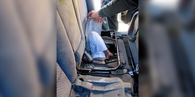 Police attempt to pull out the 19-year-old found hiding in the rear car seats.