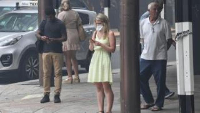 A woman wears a face mask and a summer dress in Sydney's city centre