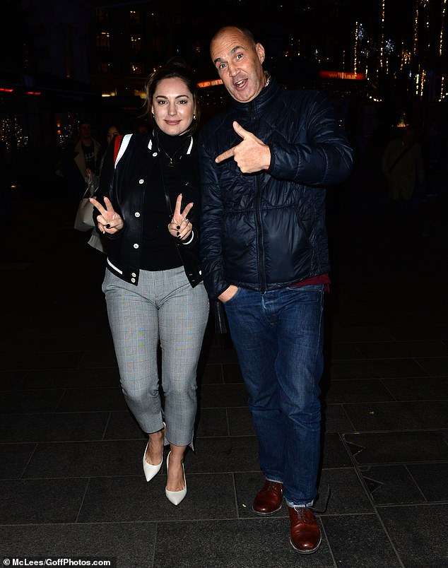 Looking good:Opting for a black roll-neck sweater and cropped grey trousers, Kelly, 40, looked typically stylish as they posed for photos on London's Leicester Square